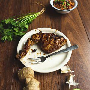 Een bord jerk chicken met eromheen de ingrediënten en een bord rijst met bonen op de achtergrond