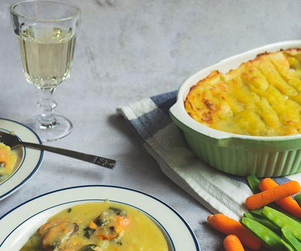 Een ovenschaal met daarin fish pie met eromheen borden opgeschepte fish pie en een glas witte wijn
