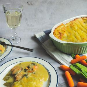 Een ovenschaal met daarin fish pie met eromheen borden opgeschepte fish pie en een glas witte wijn.