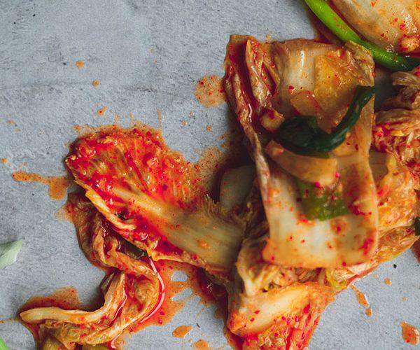 Kimchi uitgespreid over een grijze achtergrond
