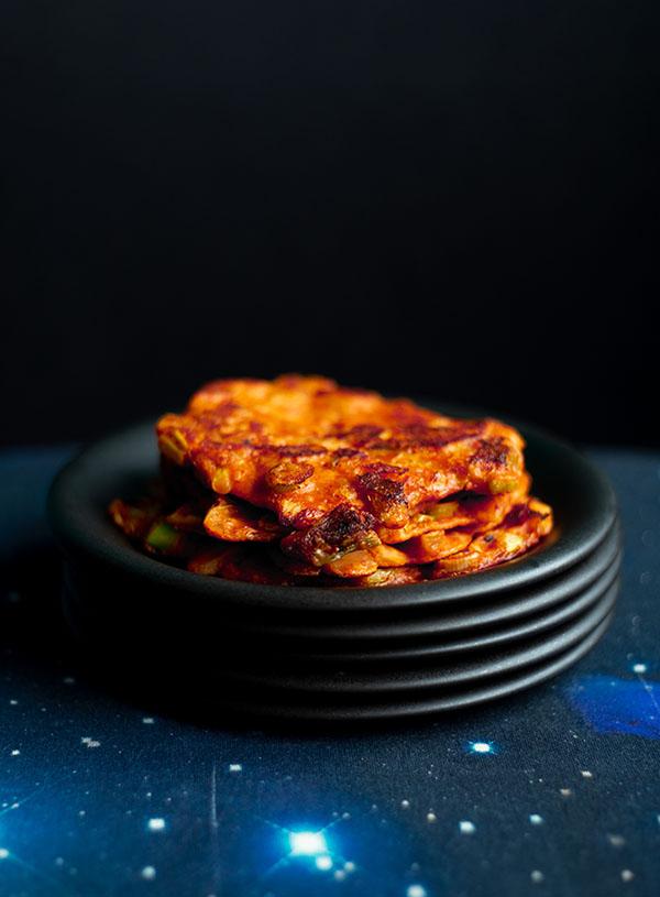 Een stapel van vijf matzwarte bordjes met daarop een stapel kimchijeon (kimchipannenkoeken).