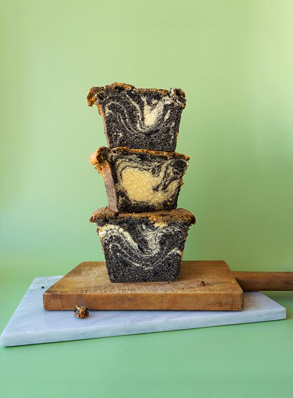 Een stapel van plakken zwarte sesam marmer cake op houten en marmeren snijplanken op een groene achtergrond