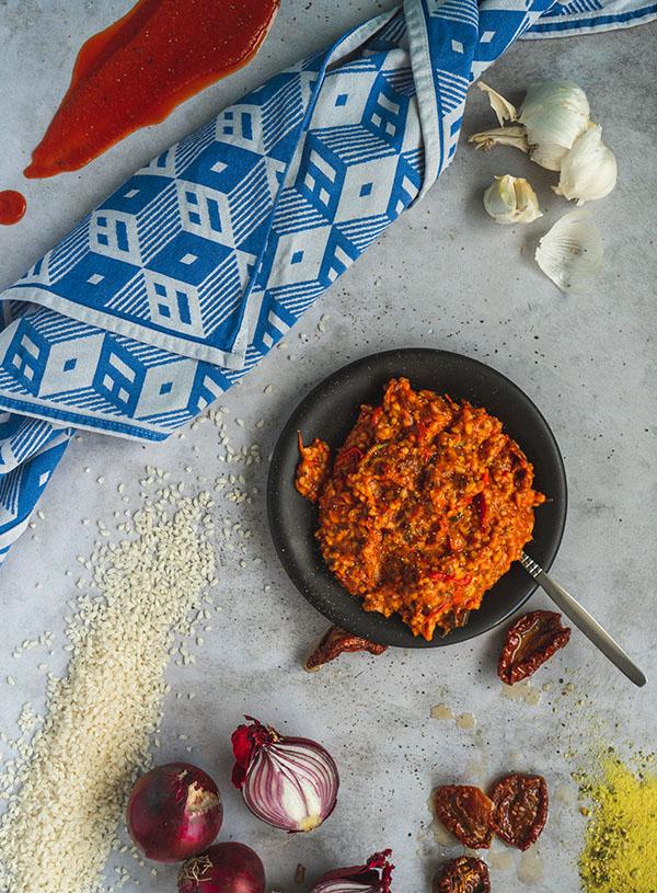 Een bord tomaten groente risotto omringt door de ingrediënten.