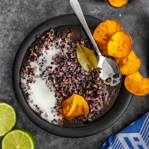 Een bord met zwarte rijstepap met pandan kokos saus en zoete aardappel chips