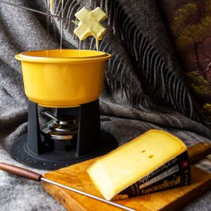 Een fonduepan met daarboven zweven twee Zwitserse kruizen druipend in kaas en ervoor een plank met extra pittige Appenzeller kaas, op een wollen deken