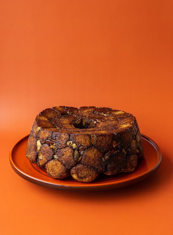 Een spekkoek gekruid monkey bread op een oranje bord.