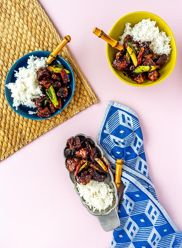 Drie borden gevuld met rijst en Mongolian tempeh met daarbij bamboevorkjes, een rieten placemat en een blauw geruite theedoek.