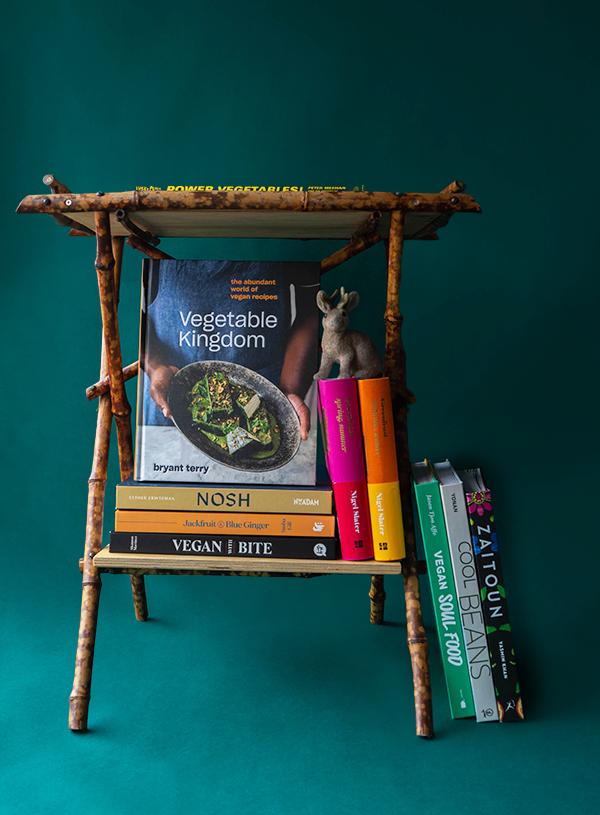 Een foto van een bamboe tafeltje met daarop en omheen diverse vegan en vegetarische kookboeken.