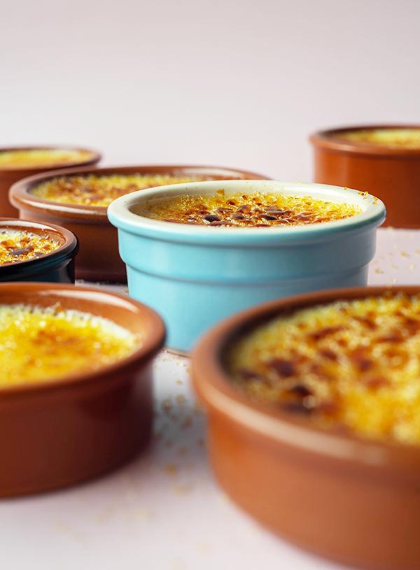 Een closeup van meerdere bakjes crème brûlée, waarvan 1 scherp en de rest uit focus.
