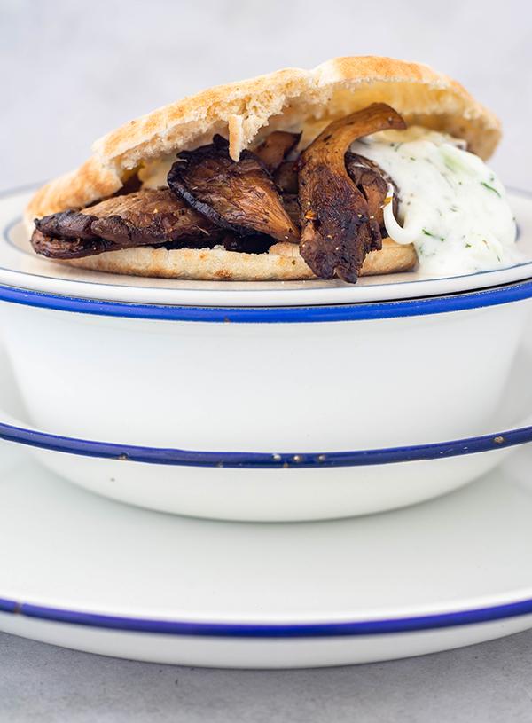 Drie blauw met witte emaille borden met daarop een verkeerd doorgesneden pita gevuld met gebakken oesterzwammen en tzatziki.