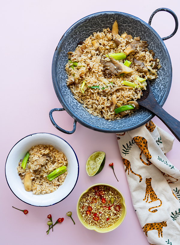 Een kleine wolkjes emaille wok gevuld met Thaise gebakken rijst met daarin een houten rijstlepel. Eronder staat een emaille bakje met rijst erin en daar weer onder een klein bakje met nam pla prik. Eromheen liggen restjes rawit, een uitgeknepen limoen en een theedoek op een roze achtergrond.