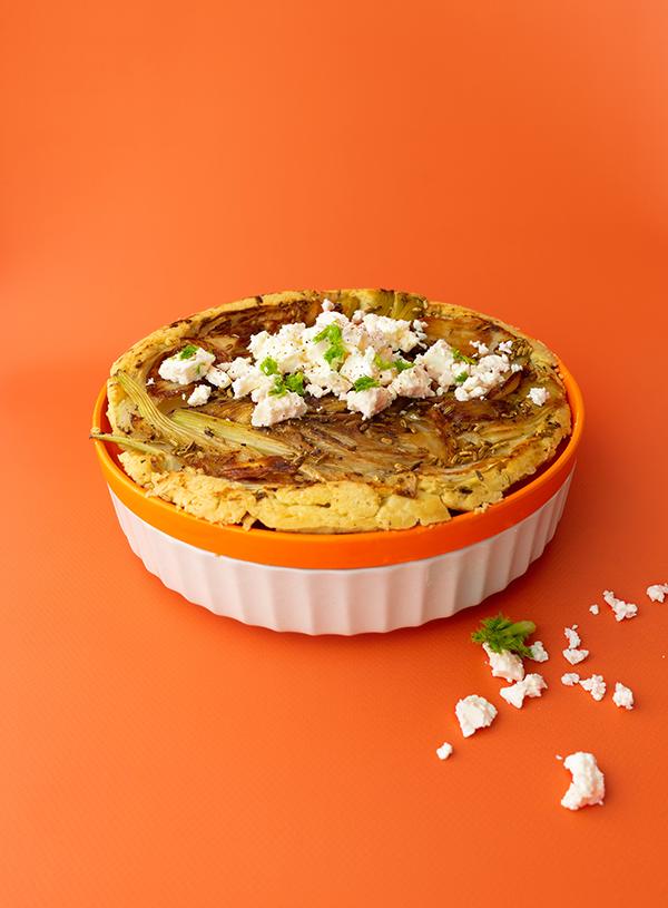 De venkel tarte tatin op een oranje en wit bord, met ervoor wat feta kruimels, op een oranje achtergrond.