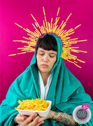 Een zelfportret van Vette Sletten geposeerd als Maria. Alleen zweeft er een kroon van patates frites om haar hoofd heen en heeft ze een bordje friet vast in plaats van Jezus.