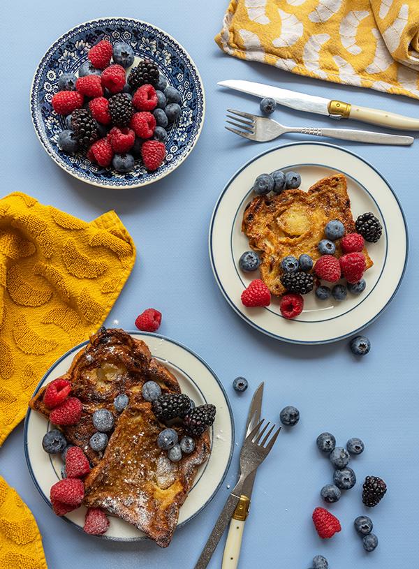 Drie wit met blauwe borjdes met daarop wentelteefjes met rood fruit op een blauwe achtergrond, met daarbij gele thee- en handdoeken gedrapeerd en nog wat rood fruit en bestek.