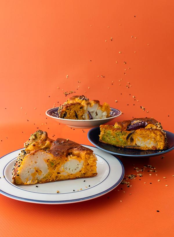Drie borden met punten broccoli bloemkool cake op een oranje achtergrond.