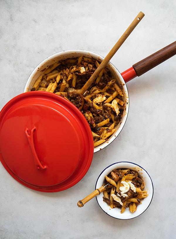 Aan grote rode koekenpan met houten handvat met daarin rigatoni pasta in rode saus met stukken mozzarella, deels afgedekt door een felrode deksel. Eronder staat een wit emaille bordje gevuld met nog meer pasta, hier steekt een bamboo vorkje uit.