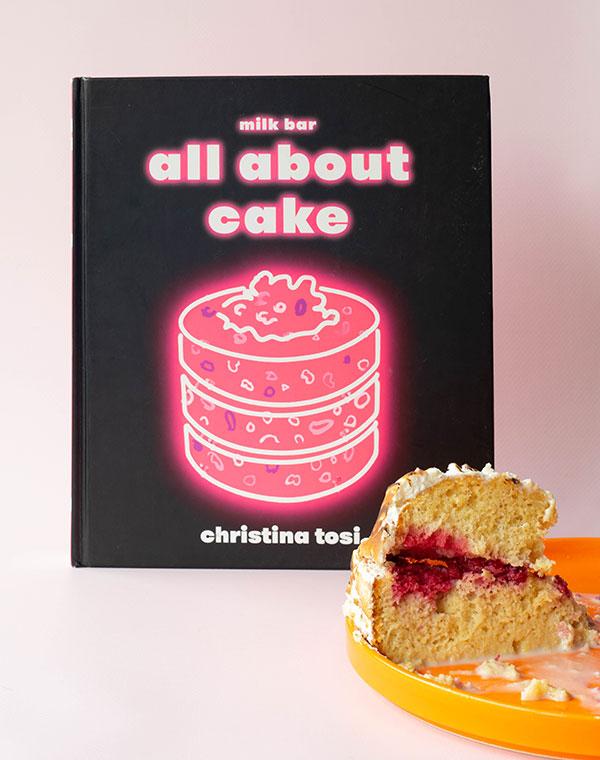Het boek All About Cake met daarbij een punt tres leches cake op een oranje bord.