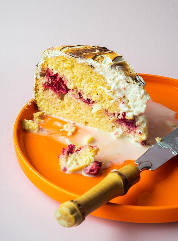Een punt pastel tres leches met kruimels en melk eromheen op een oranje bord met een bamboe-mes op een roze achtergrond.