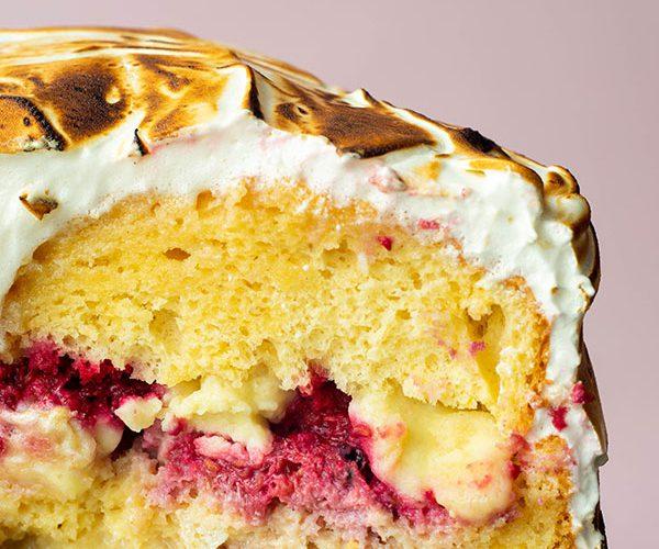 Een closeup dwarsdoorsnede van pastel tres leches met een laag cake, daarop een laag framboze en melk kruim, daarop weer een laag cake, omhult in een laag gebrande meringue.