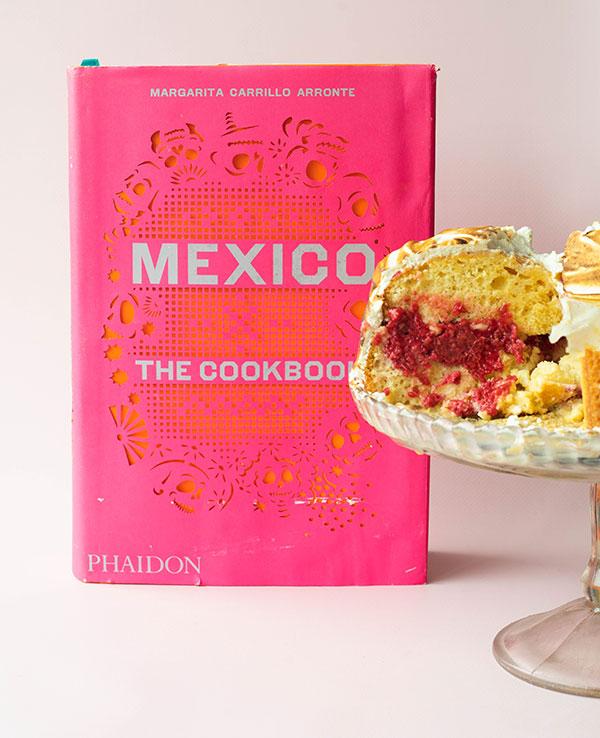 Het kookboek Mexico: The Cookbook met een hoop tres leches cake op een cake standaard.