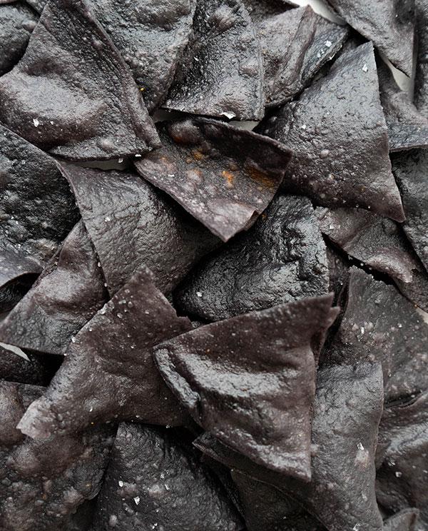 Een closeup van zwarte totopos (vers gebakken nacho chips).