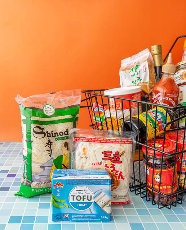 Een pak Japanse rijst, een pak verse noedels en een pak zijden tofu naast een boodschappenmandje vol spullen uit de toko.