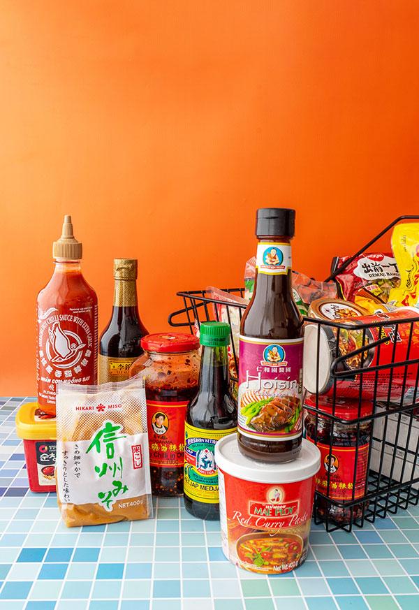 Allerlei potten, flessen, pakjes en bakjes van Aziatische ingrediënten naast een boodschappenmandje met spullen uit de toko.