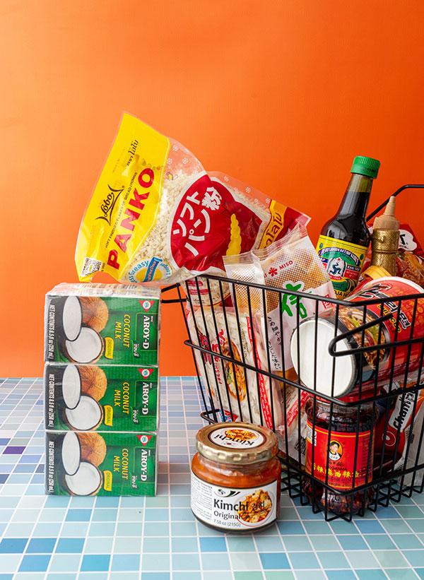 Kleine pakjes kokosmelk, een potje kimchi en een boodschappenmand vol spullen uit de toko.