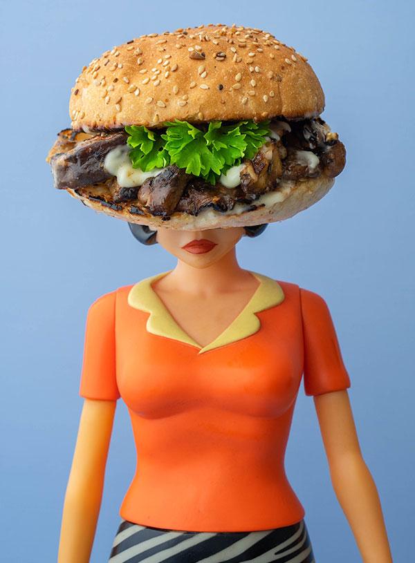 Een pop met een broodje jerk paddenstoelen met mayonaise en peterselie als hoofd.